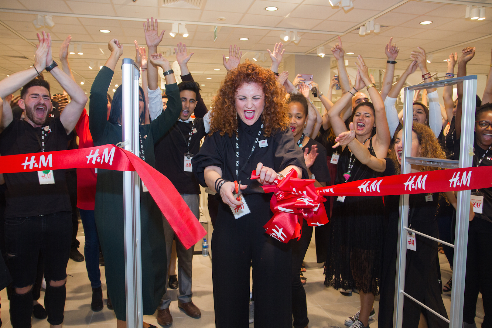 London, UK. 15th September 2016. Veronica Giannakidou, H&M Ilford manager, cuts the ribbon to official open the new store. Ilford residents and visitors queue up as a new H&M store opens its doors in Exchange Mall Ilford in Essex. Customers lined-up before 11am to receive a 25% discount wristband and enjoy music from an in-house DJ as they perused around the new store. © Elsie Kibue